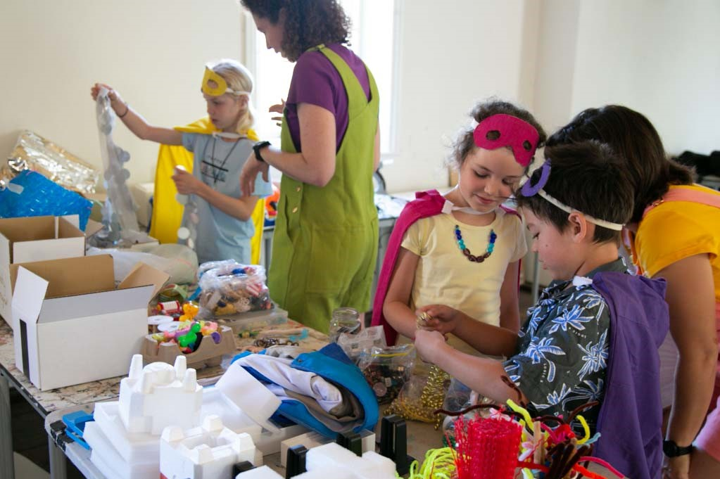 Children and adults work together on their super hero costumes. Photography by Yvonne Doherty